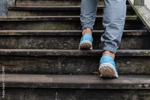 Fototapeta Women feet walking up stairs old wood. obraz na płótnie