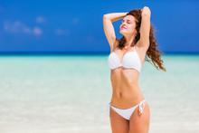 Young Woman In White Bikini Standing On The Ocean Beach