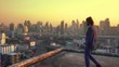 Western businessman walking to the edge of rooftop in front of Bangkok City at sunset in business concept. Thailand