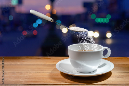 Wall Murals Cafe spoon is pouring sugar on coffee cup with saucer on wooden table on night blur background