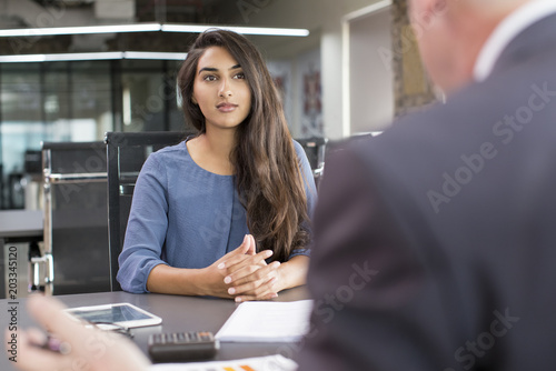 Photo Focused Indian female customer meeting with financial advisor