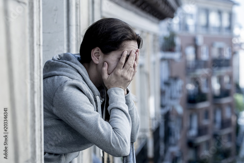 Fotografia  young beautiful Latin woman looking sad and depressed on a balcony in a depression concept