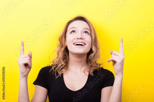 Fotografía  Happy smiling woman pointing up on yellow background in studio photo