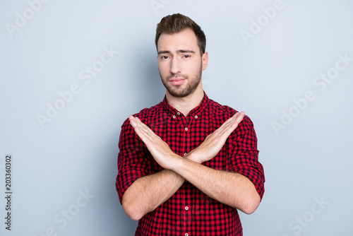 Let's make a stop I don't want to listen to your lie! Portrait of unhappy depressed unsatisfied troubled annoyed guy crossed his hands, isolated on gray background