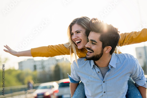 Fotografie, Obraz  Couple in love having fun carrying piggyback - freedom concept