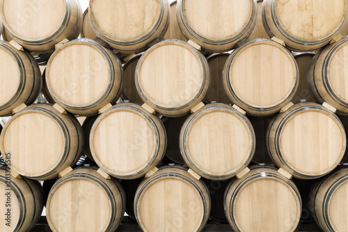 Photo Wine barrels stacked in the old cellar of the winery