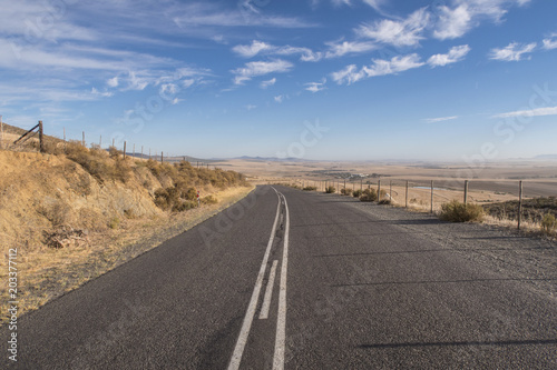View of long open road at sunrise in arid landscape