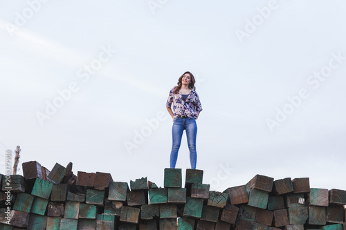 Fotografie, Obraz  portrait of a young beautiful woman wearing casual clothes, standing on a mountain of green wood blocks background and smiling