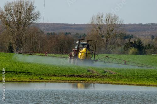 Fotografía Farmer on tractor spraying green wheat field