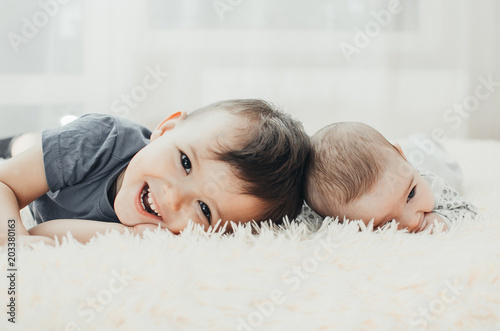 Photo cute kids brother and sister lie on their stomach and touch their heads
