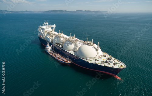 A small tanker on the roadstead bunkers a large LNG tanker.