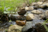 Fototapeta Kamienie - Stones balance near river  in wild nature. Pebbles stack by stream in forest.