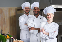 Multiracial Chefs Team Posing With Folded Arms On Kitchen