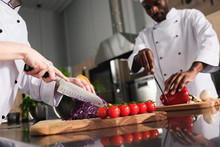 Multiracial Chefs Team Cutting Raw Vegetables In Kitchen