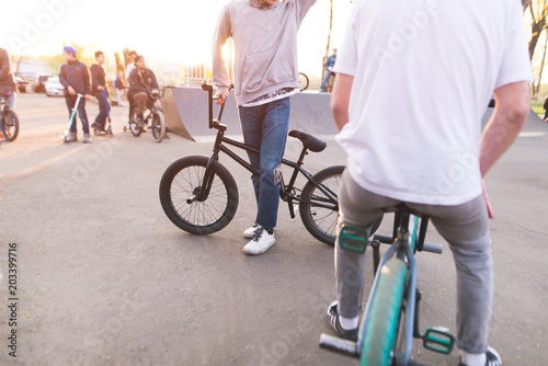 Company bmx riders in a skate park on the background of the sunset. Training young people on a bmx bike. bmx concept