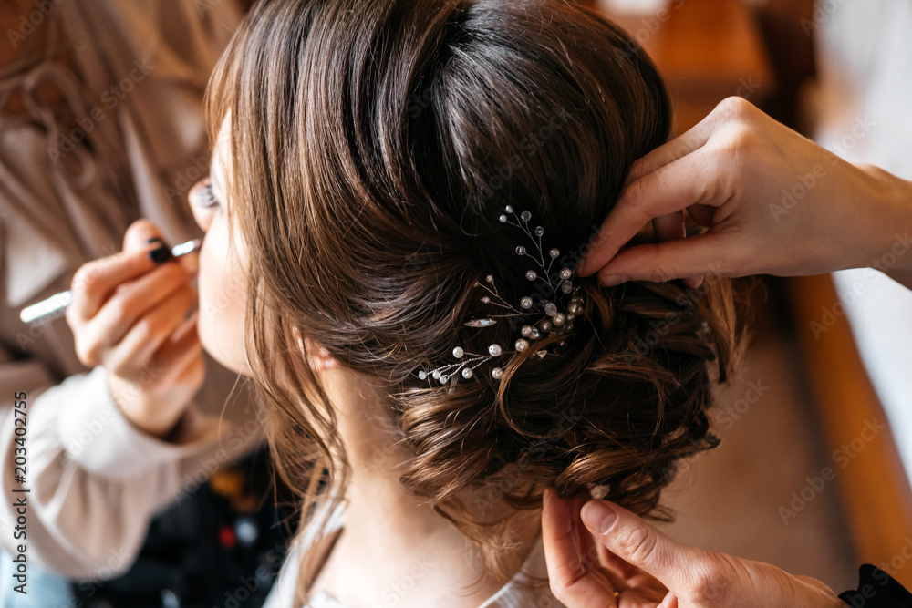 Fototapeta A hair stylist and make-up artist prepare a bride for the wedding day