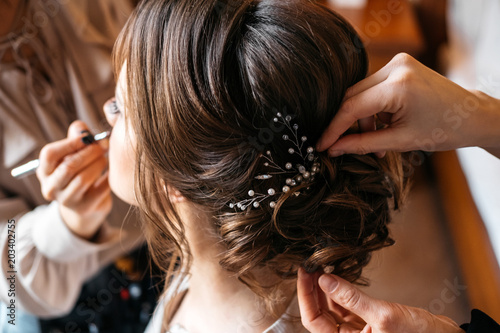 Foto op Plexiglas Kapsalon A hair stylist and make-up artist prepare a bride for the wedding day