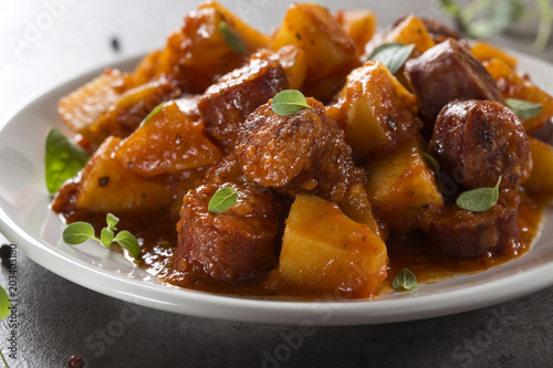 Potatoes stew with pork sausage slices and tomato sauce on plate with oregano leaves
