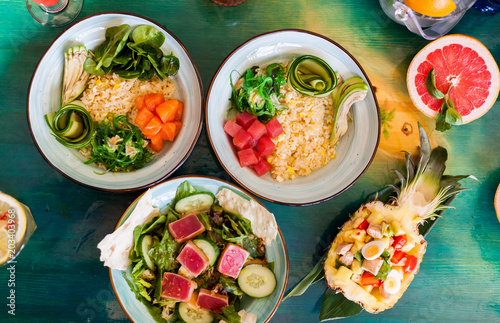 Salads from fresh products with meat, fish, chicken and vegetables on the table among colorful refreshing cocktails with ice Canvas-taulu