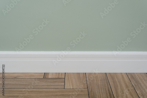 Photo Light green matte wall, white baseboard