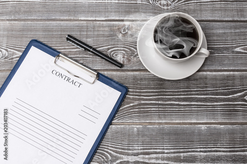 Fényképezés  ccup of coffee, pen, contract form on a wooden background