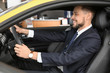 Young businessman sitting in driver's seat of auto. Buying new car