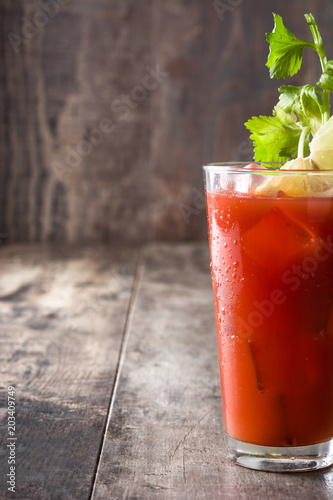Tuinposter Cocktail Bloody Mary cocktail in glass on wooden table.