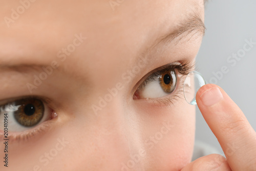 Photo Little child putting contact lens into his eye, closeup
