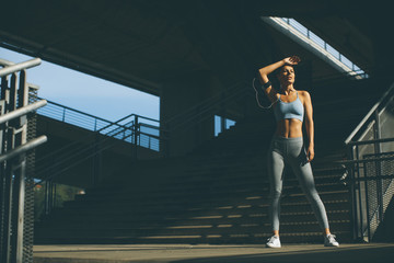 Fototapeta Young smiling female resting after an active fitness training