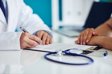 Male doctor consults with his patient and writes notes on the clipboard