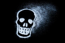 White Sugar In Shape Of The Skull Isolated On Black Background. Caution Sign. Deadly Addiction