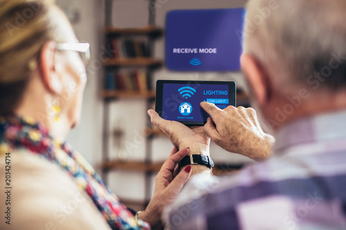 Fotografía  Elderly couple sitting comfortably on a sofa with their backs holding remote hom