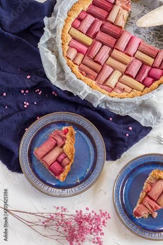 Rhubarb pie, cake, tart. White background, blue plates and napkin.
