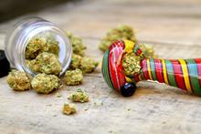 Colorful Marijuana Pipe With A Jar Of Marijuana On Wood Table (Sativa Dominant Hybrid, Green Crack Strain)