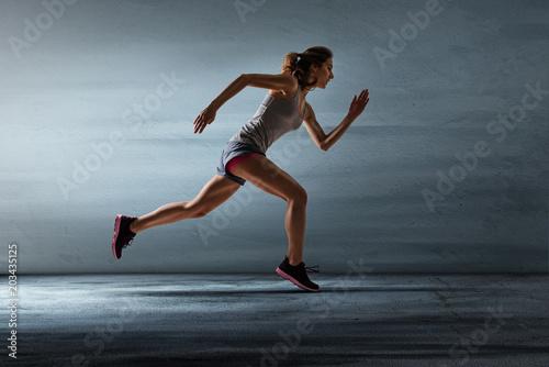 Läuferin vor grauer Wand