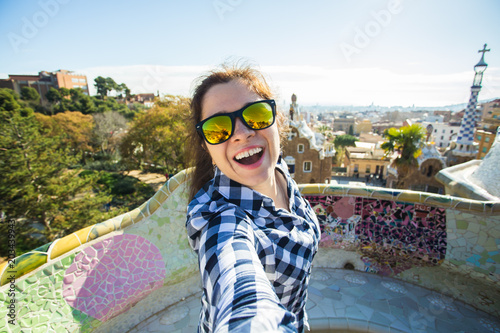 Fotografie, Tablou  Young happy woman making selfie portrait with smartphone in Park Guell, Barcelona, Spain