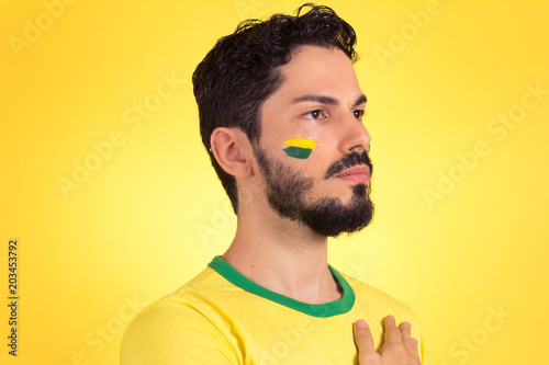 Brazilian supporter of National Team of football is listening to National anthem with hand on the chest Canvas Print