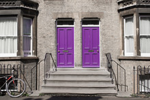 Two Identical Pink Purple Wooden Front Doors At The Entrance Of A Classic Victorian British Style House