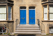Two Identical Blue Wooden Front Doors At The Entrance Of A Classic Victorian British Style House
