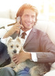 business man talking on the phone and holding his pet