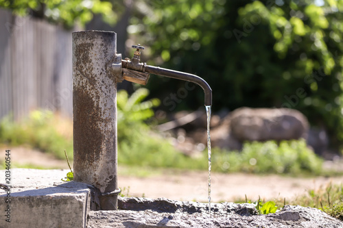 Fotobehang Tap with pouring water outdoors. Water scarcity concept