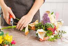 Female Florist Pruning Stem At Table
