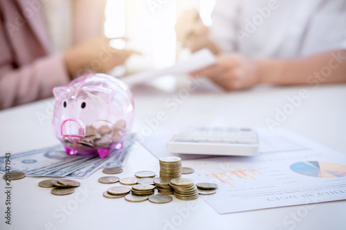 Fototapeta Two couples putting coins into piggy bank, writing to report and using calculator to analysis business investment strategy with income of money coin and dollar, financial concept obraz