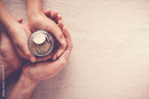Fotografía  child and adult holding money jar, donation, saving concept