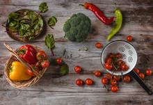 Top View Of Wicker Basket, Plate, Colander, Cherry Tomatoes, Peppers, Mangold Leaves And Broccoli On Wooden Table