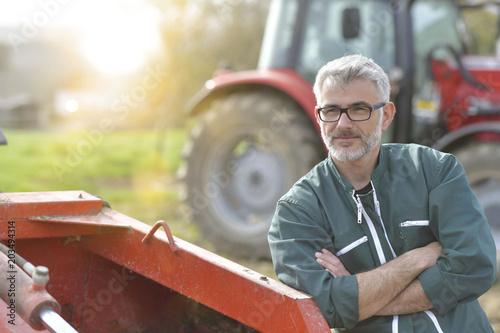 Fototapeta Farmer standing by tractor outside the barn obraz
