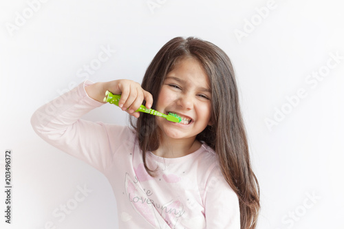 Fotografía  Little cute child girl brushing her teeth on white background