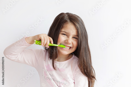 Little cute child girl brushing her teeth on white background  Space