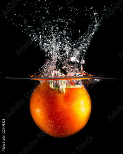 czerwony-pomidor-w-wodzie-na-czarnym-tle