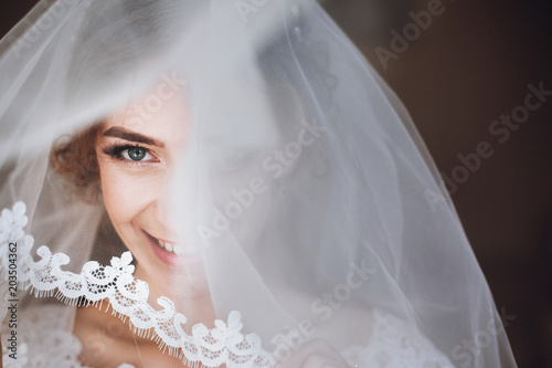 happy stylish bride smiling and looking under veil Fotobehang